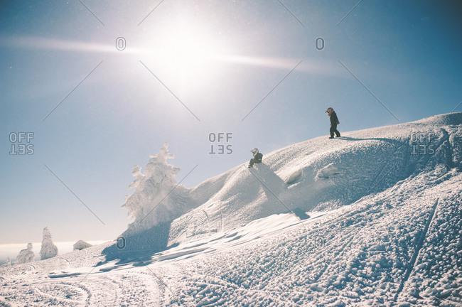 Kids wearing helmets sliding down snowy hills