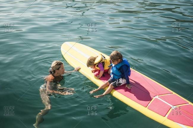 Mother showing her children a stand-up paddleboard