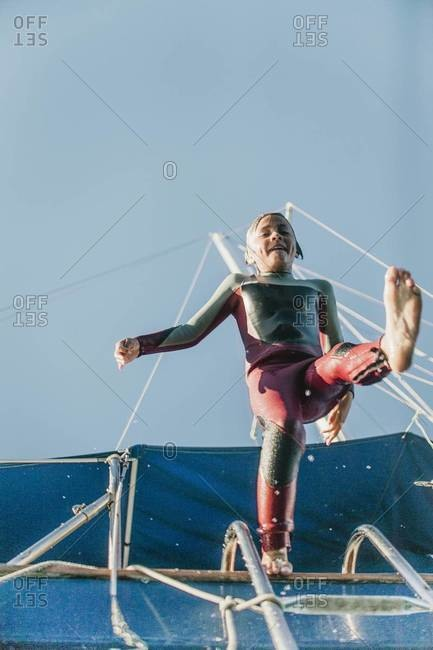 Boy in a wetsuit leaping off a sailboat