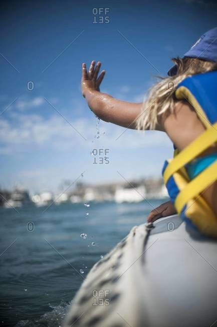 Girl in a dinghy splashing water with her hand