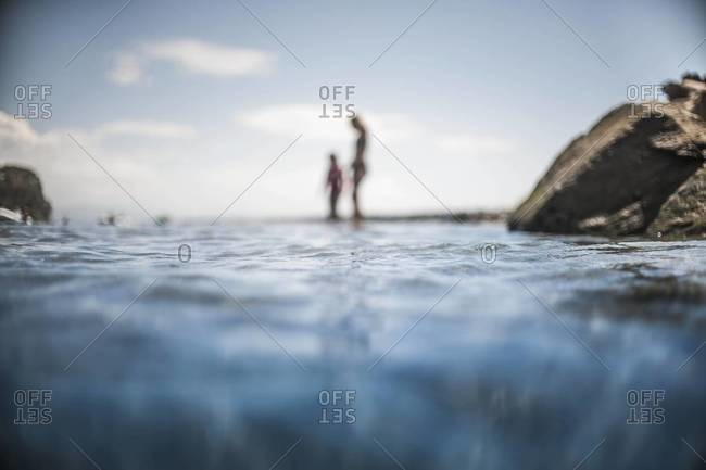 Mother and child standing on the seashore