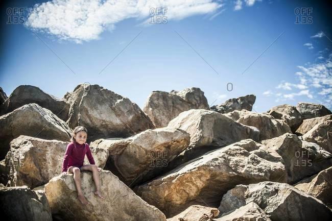 Little girl sitting on coastal rocks