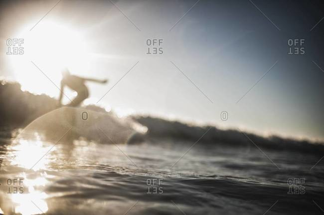 Silhouette of a boy surfing in San Clemente, California