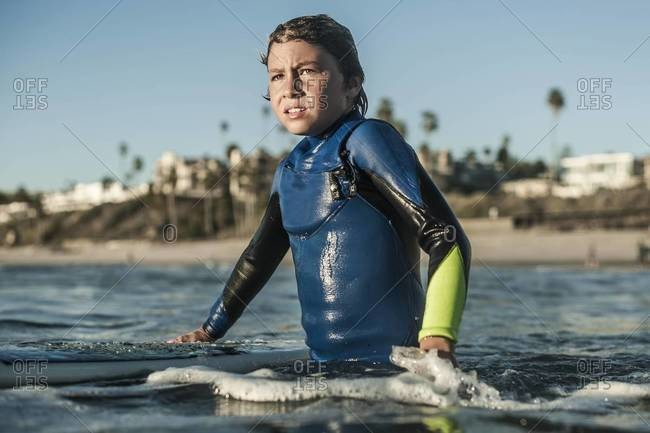 Boy looking out at waves while surfing in San Clemente, California