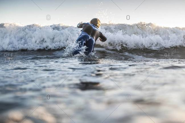 Young surfer boy diving into a wave in San Clemente, California