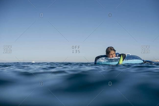 Boy relaxing on a float in the ocean in Catalina, California