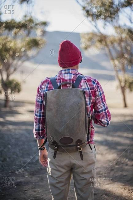 Man wearing a backpack taking a hike