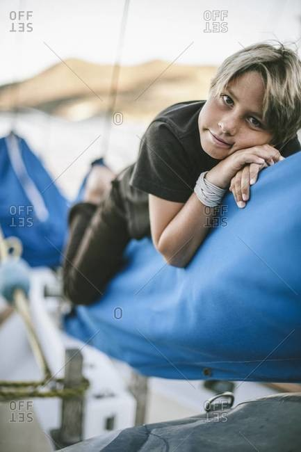 Boy resting on the sails of a sailboat
