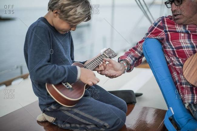 Father teaching his son how to play ukulele
