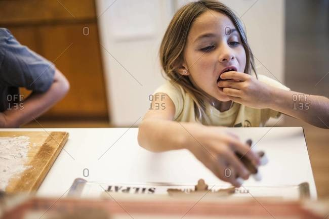 Girl eating just baked holiday cookies