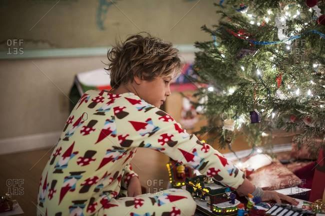 Boy in his pajamas opening presents under tree
