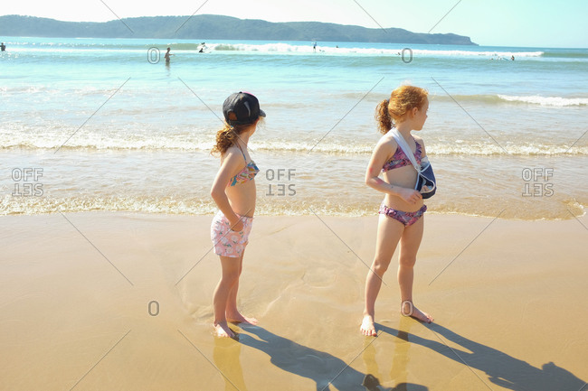 Girls standing in the surf at the beach