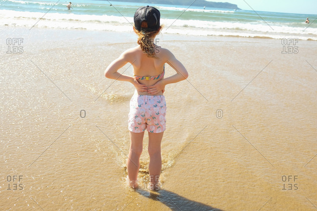 Girl looking out at the ocean from beach