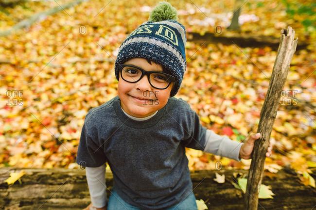 Portrait of boy wearing winter beanie hat holding a stick