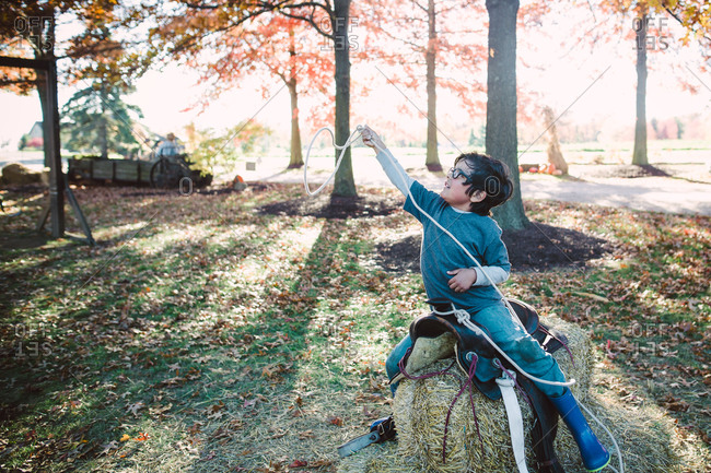 Little boy on a horse saddle over bale of hay with a lasso