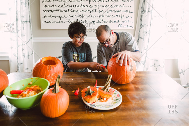 Father and son carving a pumpkin together