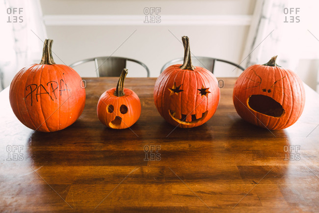 Carved pumpkins lined up on a wooden table