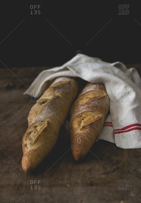 Still life of fresh baguettes in a white tea towel