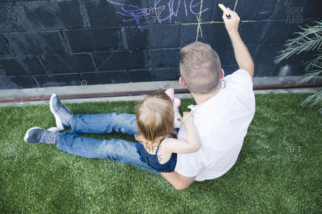High angle view of father and daughter drawing on a black painted wall with chalk