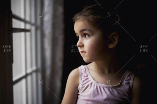Girl gazing wistfully out window