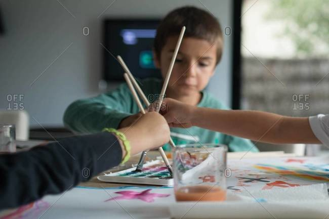 Boy and children painting with watercolor
