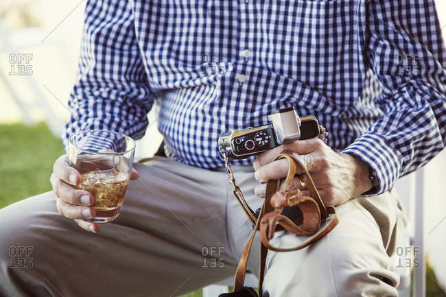 Lap of man holding drink and camera