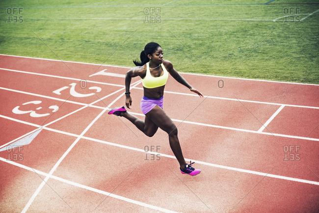 Female runner sprinting down track