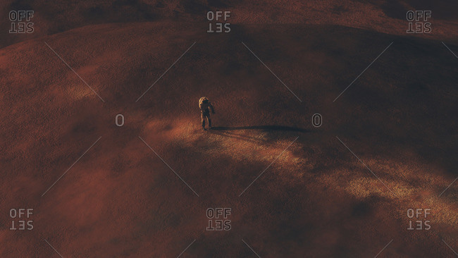 Astronaut walking on the surface of a red planet