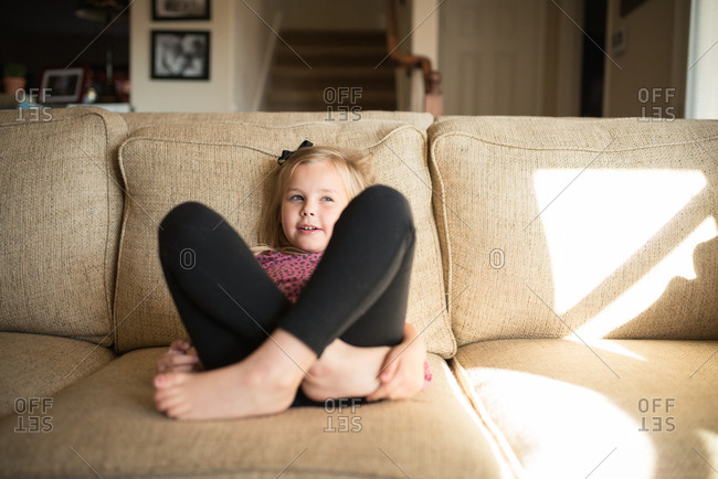 Little girl sitting on a couch with her legs crossed and knees up