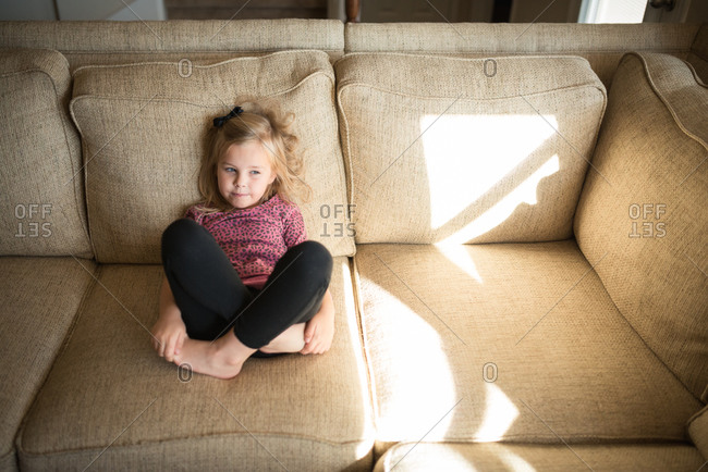 High angle view of a little girl sitting on a couch with her legs crossed