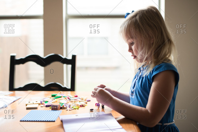 Little girl standing at a table playing with small toys