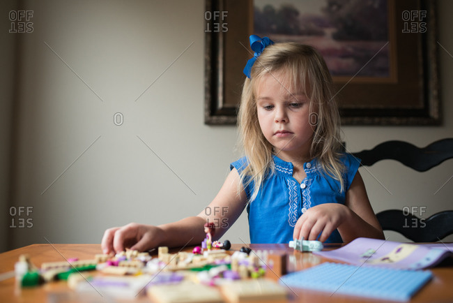 Little girl playing with small blocks