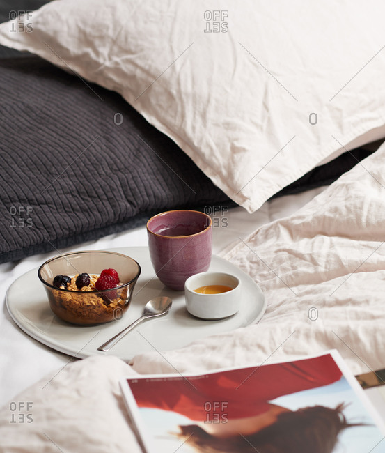 Breakfast tray of granola on a bed with bedding and pillows
