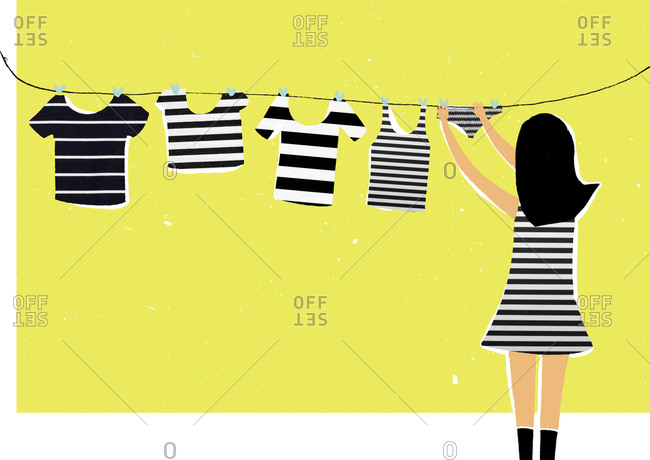 Woman in striped dress hanging striped laundry on line