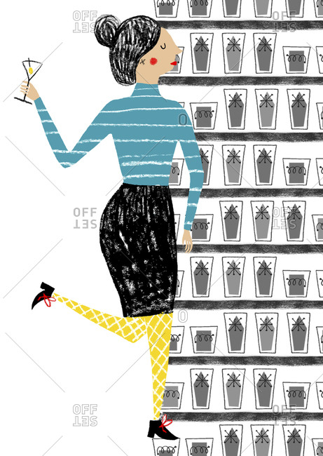 Stylish woman with cocktail standing next to wall of glassware