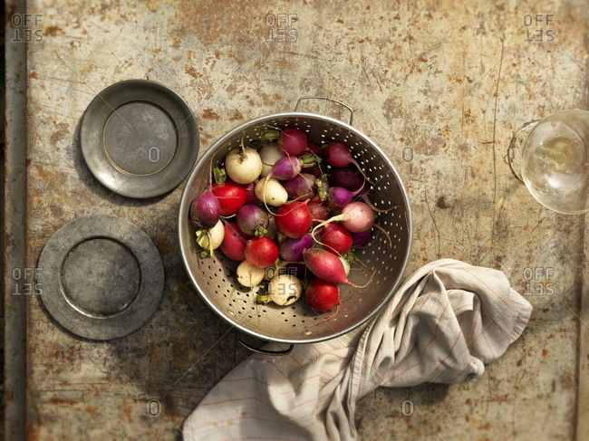 White and red radishes in a strainer
