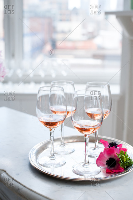 Wine glasses on a serving tray with pink flowers