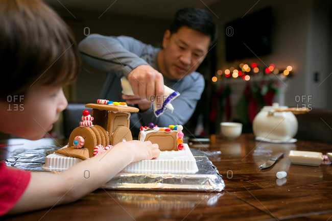 Father squeezes icing onto gingerbread train while son watches