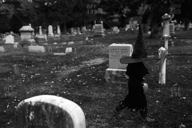 Black and white of a little girl dressed as a witch walking through the cemetery