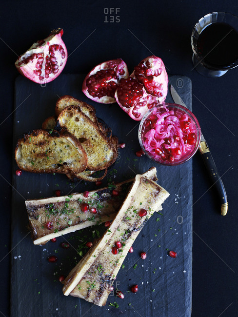 Bones with marrow, toast, and pomegranate seeds