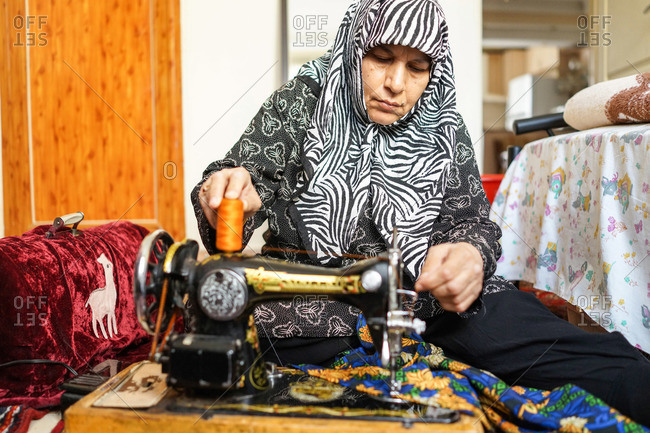 Tehran, Iran - March 20, 2013: Elderly woman sewing a dress at home using a manual machine