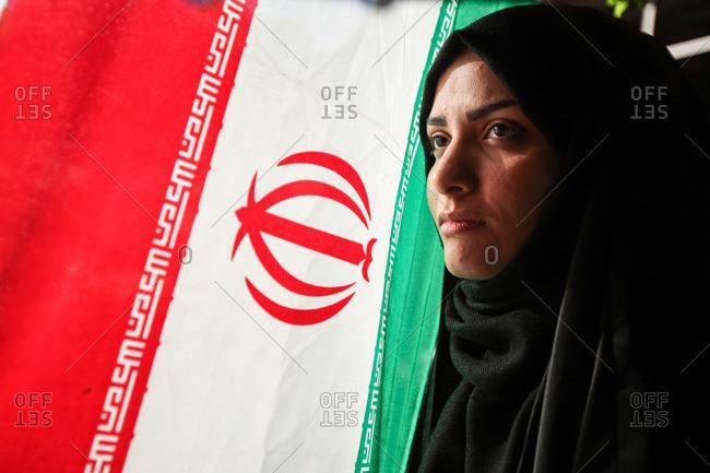 Tehran, Iran - April 22, 2013: Proud and beautiful Iranian woman next to the flag