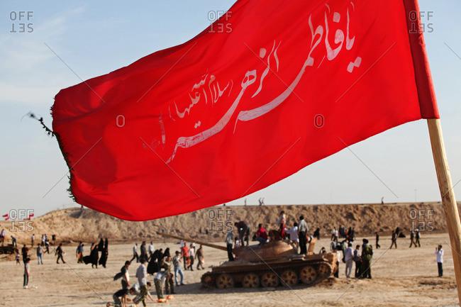 People and tank near flag from the Iran-Iraq War, Ahwaz, Iran