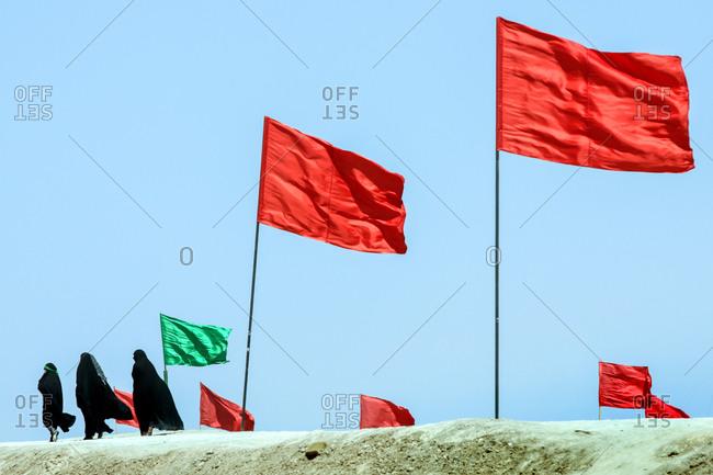 Women visiting a battlefield with traditional Iranian flags of the Iran-Iraq war near border, Ahwaz, Iran