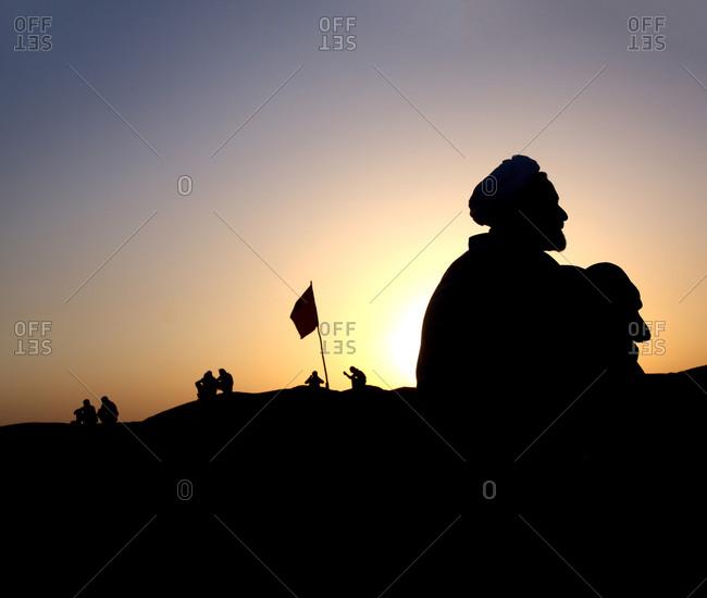 Ahwaz, Iran - March 18, 2013: Elderly mullah sitting on the Iran Iraq border at sunset