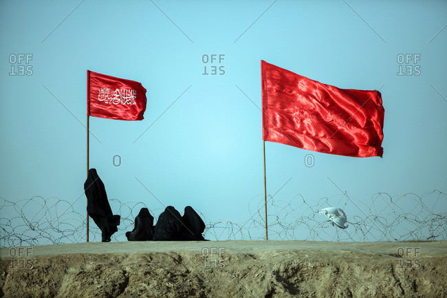 People visiting a battlefield with traditional Iranian flags of the Iran-Iraq war near border, Ahwaz, Iran