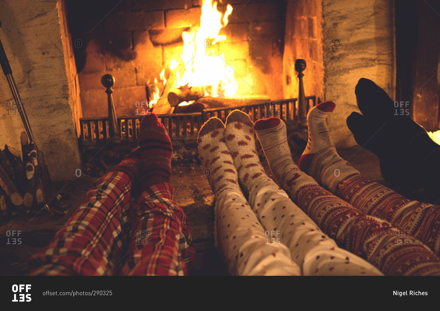 People in colorful socks and pajamas warm their feet in front of ...