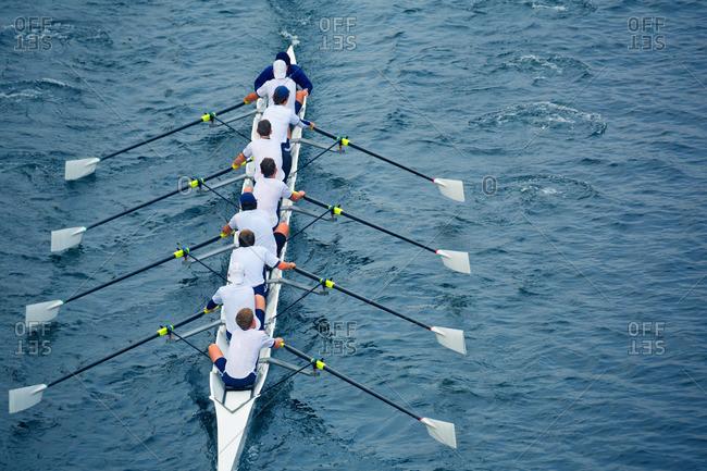 Crew team rowing across water
