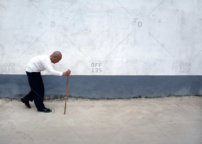 Guilin, China - October 16, 2012: Old man walking hunched over