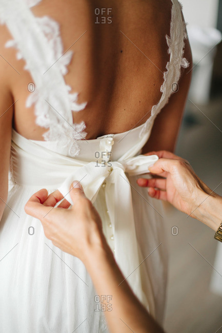 Back view of woman tying bridal gown
